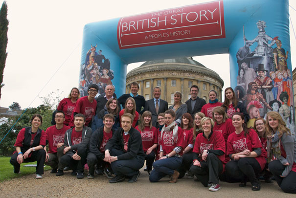 Great British Story team photographed in front of inflatable arch