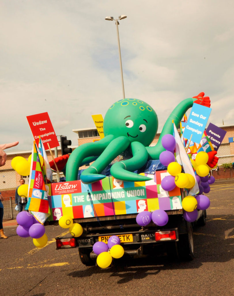 Inflatable baby octopus riding in the back of a lorry