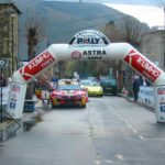 Rally cars on road with race arch