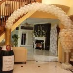 Giant replica Champagne bottle with balloon arch and glass