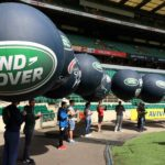 People with Land Rover rugby spheres receiving briefing