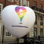 #LoveHappensHere giant white inflatable heart with rainbow design in street