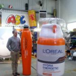 Man standing next to inflatable product replicas for L'Oréal