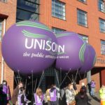 3 giant Unison parade balloons attached to people in the street