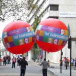 People walking in street with Usdaw parade balloons