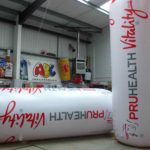 2 giant inflatable replica water bottles for PruHealth with man holding ropes