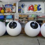 4 large white push balls with black circle containing white dots in ABC Inflatables workshop