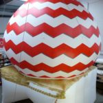 Man hand painting gold base to giant inflatable dome