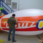 Man painting green lettering onto Ozmen blimp