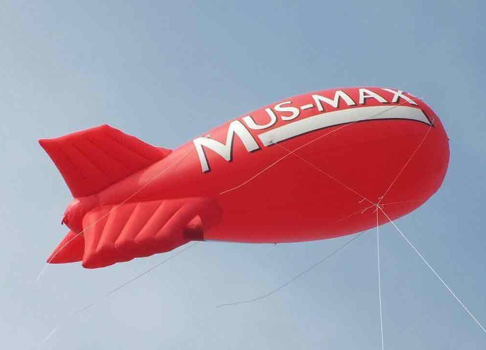 Mus-Max red blimp flying in a blue sky
