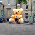 Giant inflatable yellow bear by large house with people in front.
