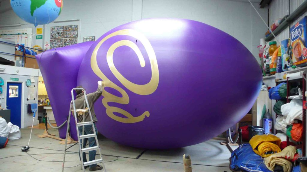 Painting the logo on the bespoke inflatable Easter Egg for Cadbury