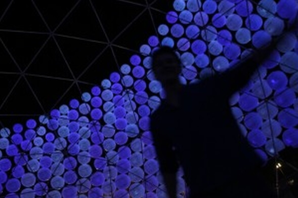 silhouette against blue lit inflatable spheres inside dome at night