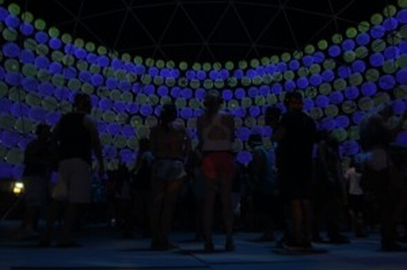 festival goers inside dome of inflatable spheres lit at night
