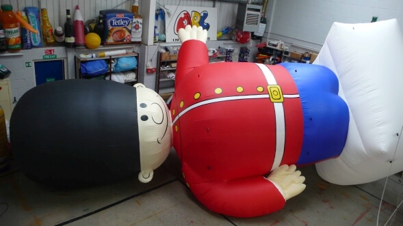 inflatable guardsman lying on his side in workshop