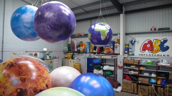 Giant inflatable planets suspended from workshop ceiling