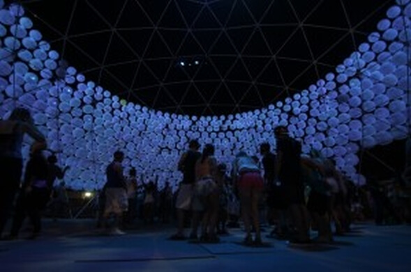 silhouetted people inside lit dome at festival