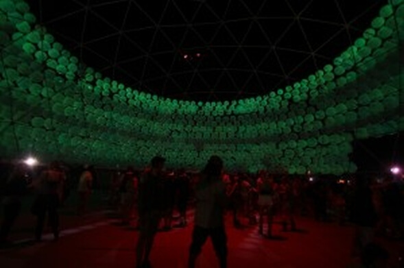 silhouetted people inside green lit dome at night
