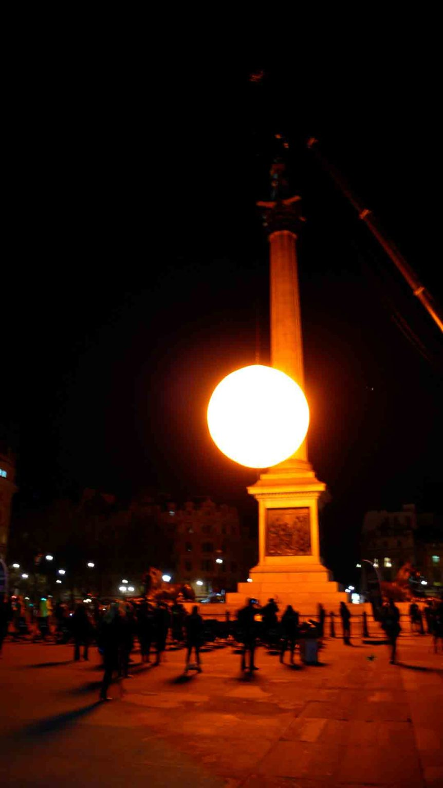 People watching inflatable sun in the dark at Trafalgar Square