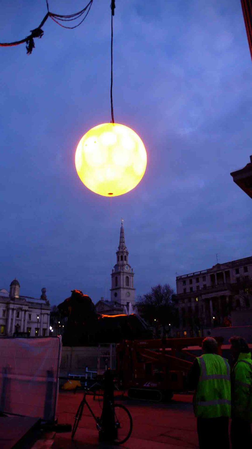 Inflatable moon light suspended with city skyline behind