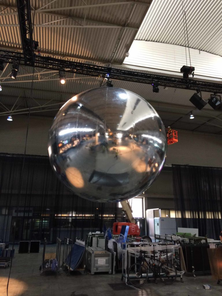 one giant inflatable mirror balls suspended from ceiling