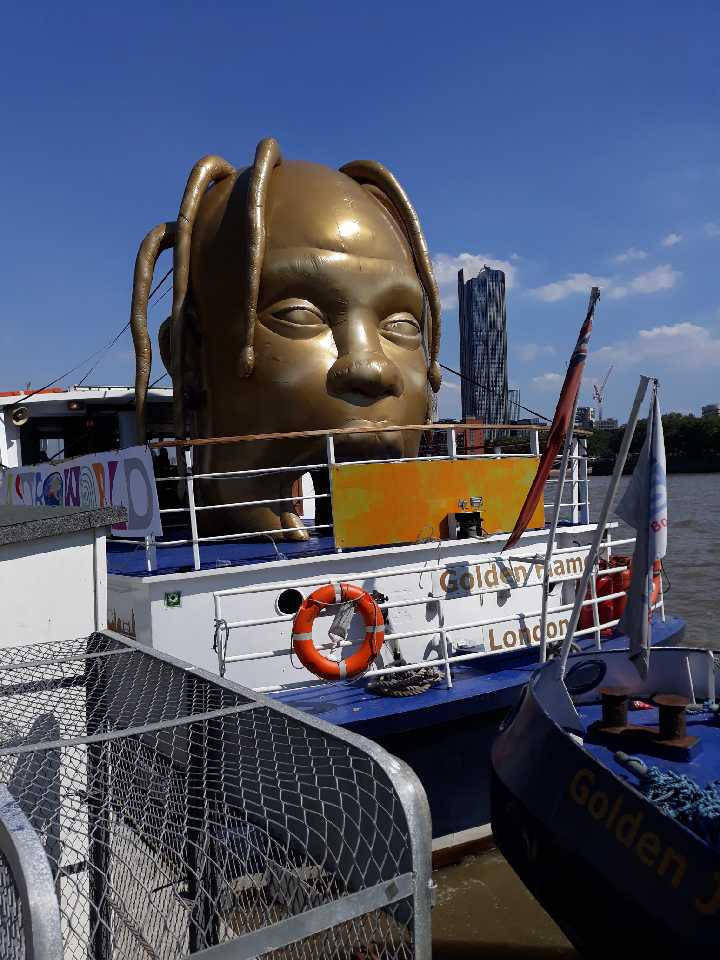 Travis Scott gold inflatable head on boat on River Thames