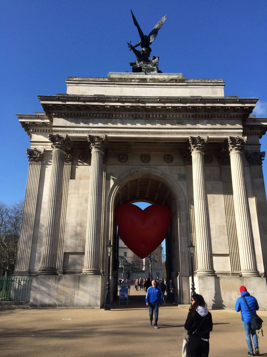 People in front of Wellington Arch with inflatable heart in the arch