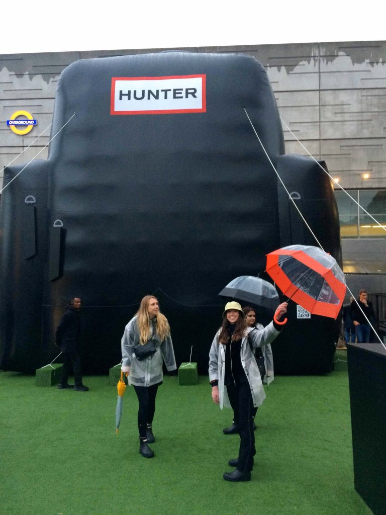 People with Hunter boots and umbrellas in front of giant backpack inflatable